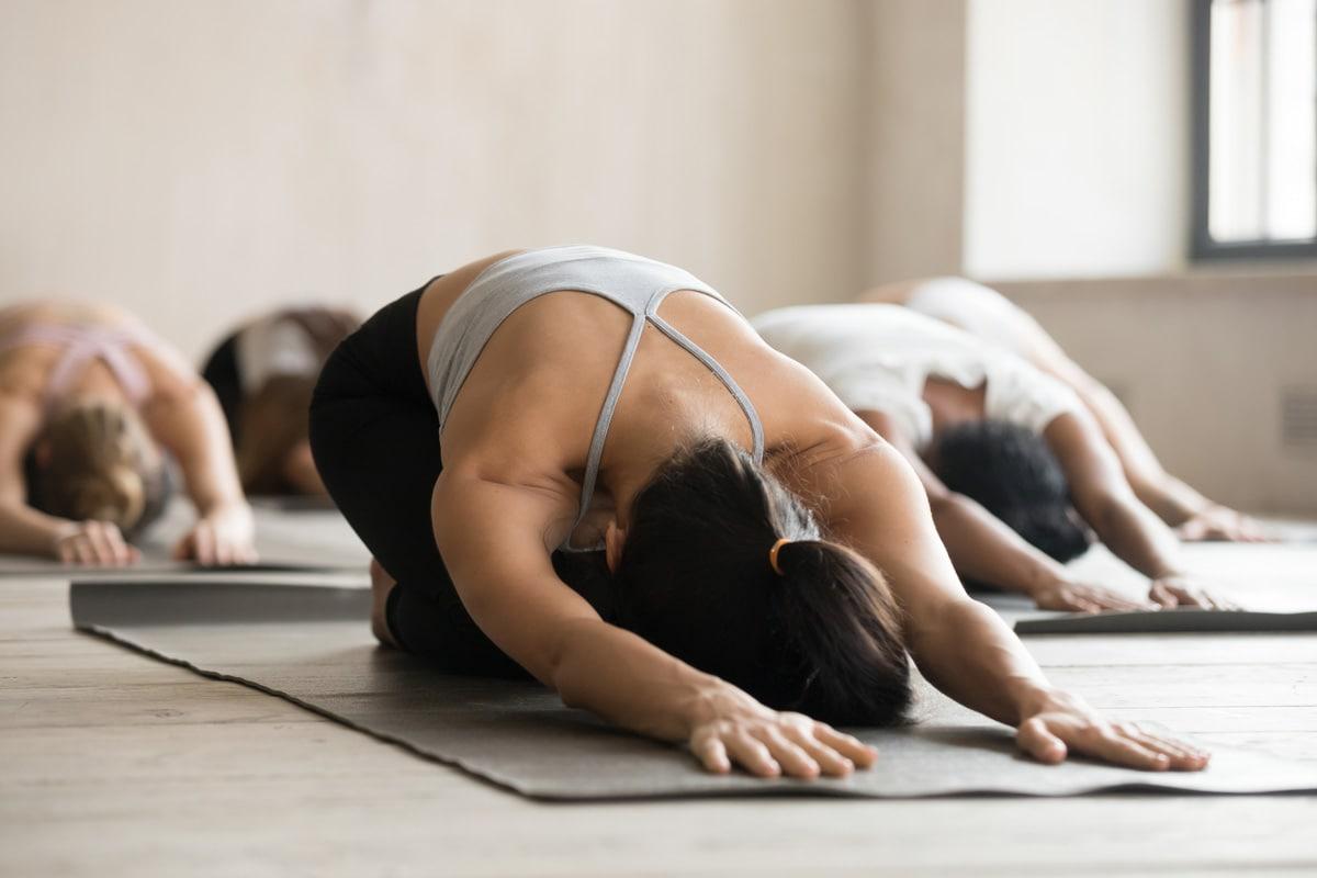 Yoga - Gruppenübung mit 6 Frauen alle sind auf den Kien und der Kopf und die Hände berühren den Boden