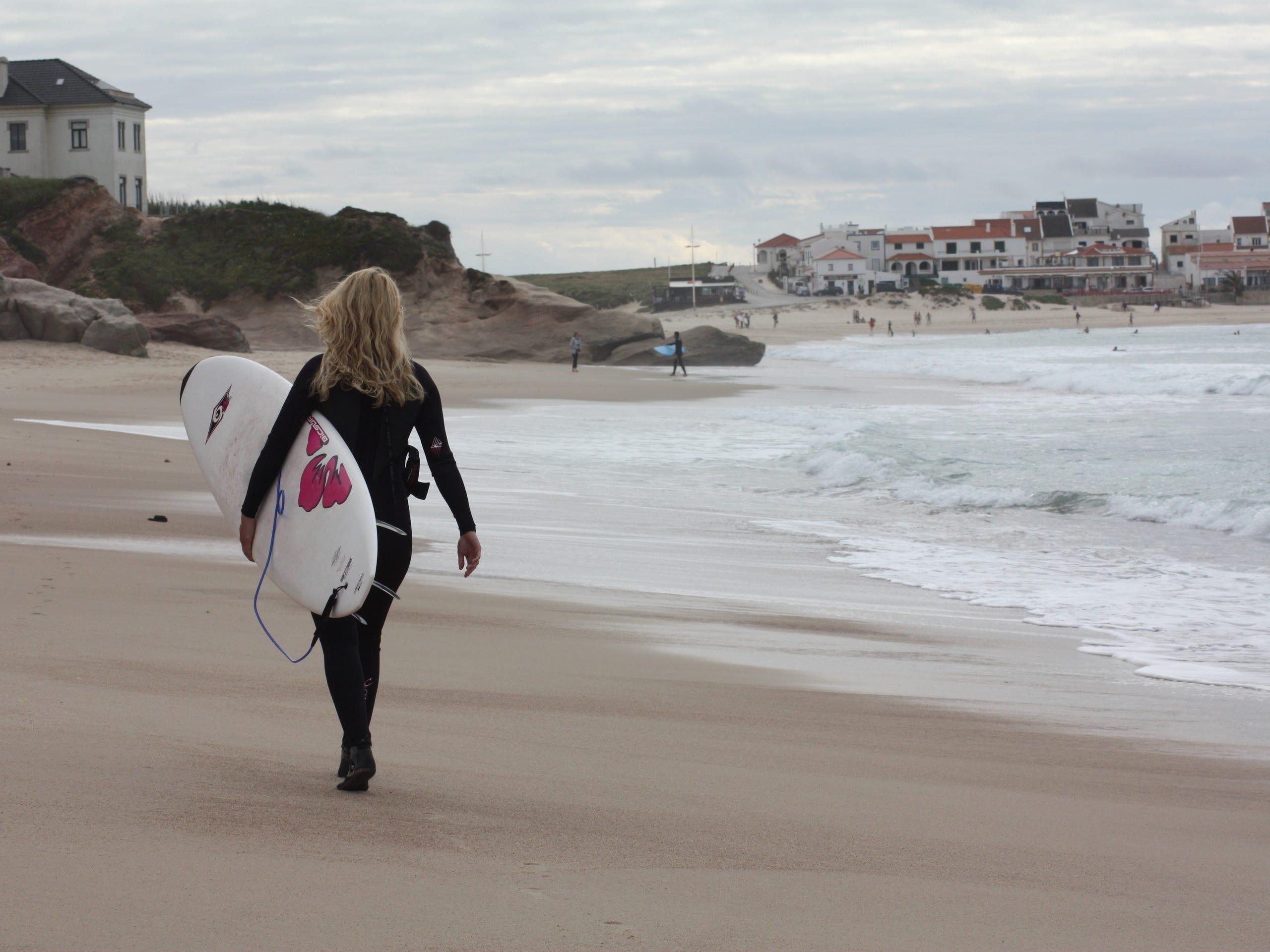 Steffi von Aloha Lifestyle hat Ihren Surf Outfit an und Ihr Surfbrett unterdem linken Arm und läuft am Strand entlang