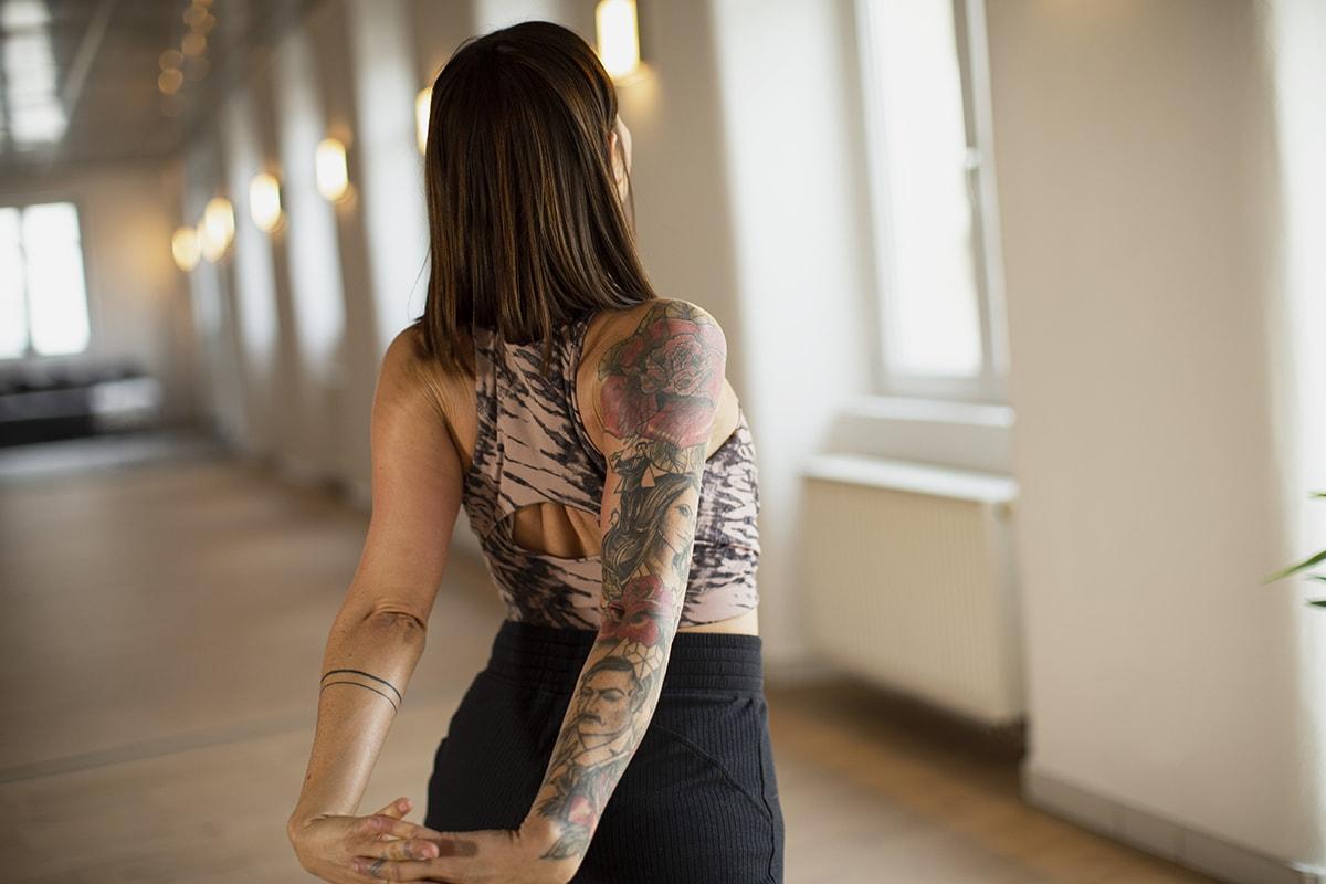 Stephanie Muley zeigt eine Pilates Übung mit verschränkten Händen hinter dem Rücken